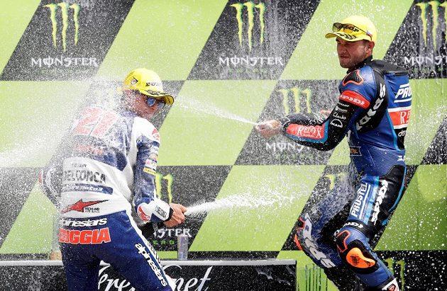 Tradiční oslava na stupních vítězů. Vpravo Jakub Kornfeil stříká šampaňským po vítězi závodu v kategorii Moto3 Fabiu Di Giannantoniovi.