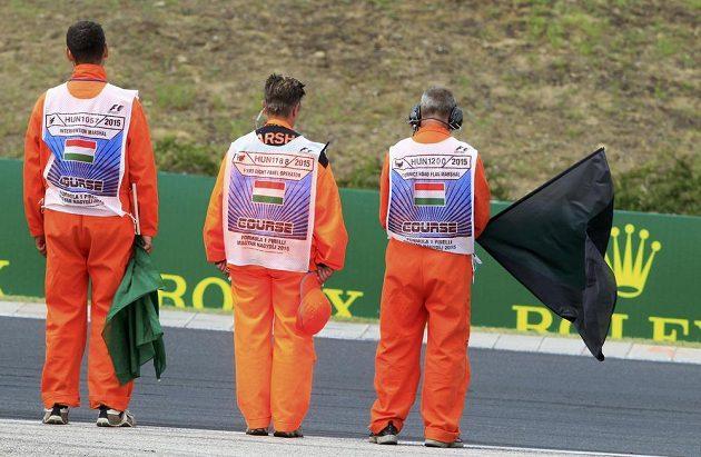 Traťoví maršálové drží minutu ticha za Julese Bianchiho před startem GP Maďarska.