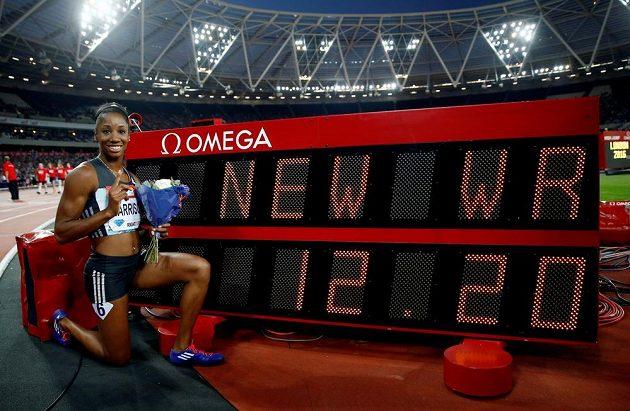 Rozesmátá Kendra Harrisonová pózuje u tabule s hodnotou svého nového světového rekordu.