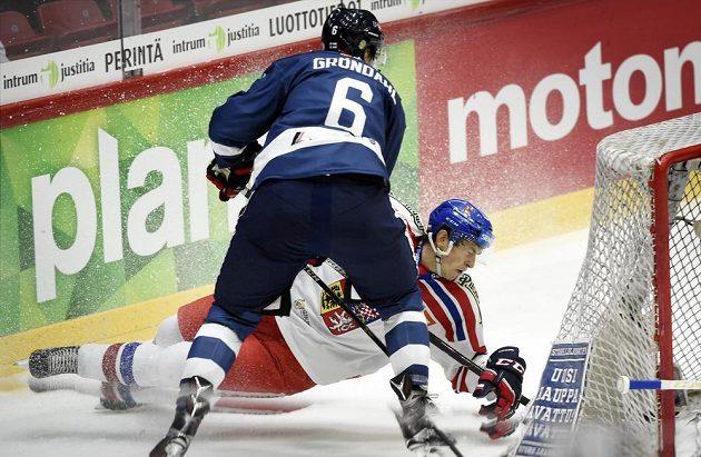 Po hokejce finského obránce Ari Grondahla (vlevo) se sesunul k ledu český bek Tomáš Dvořák.