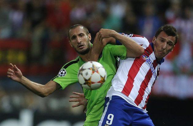 Obránce Juventusu Giorgio Chiellini (vlevo) bojuje o míč útočníkem Atlétika Madrid Mandžukičem.