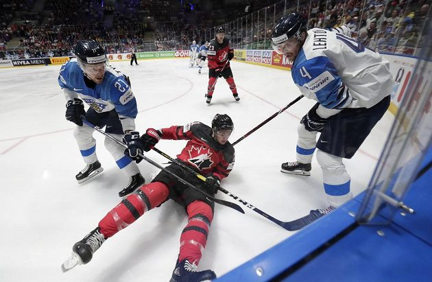 Finále hokejového MS v plném proudu. V souboji u mantinelu Kanaďan Anthony Cirelli mezi Finy Juhani Tyrvainenem a Mikko Lehtonenem (vpravo).