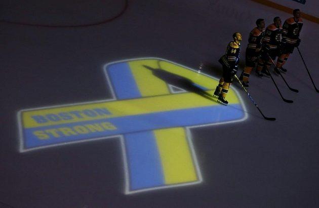 Bostonští hokejisté v čele s Dennisem Seidenbergem (44) při ceremoniálu k uctění obětí teroristických útoků při bostonském maratonu před duelem s Buffalem.