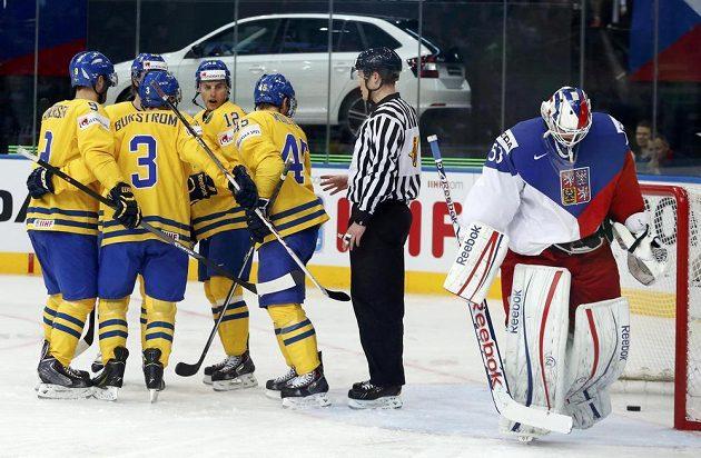 Zklamaný český brankář Alexander Salák (vpravo) krátce po inkasovaném gólu, který oslavují v boji o bronz hokejsité Švédska.