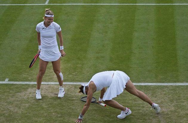 Česká tenistka Marie Bouzková se směje své krajance Lucii Hradecké poté, co upadla na trvanatém kurtu ve čtvrtinále Wimbledonu.