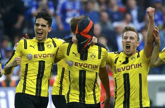 Maskovaný dortmundský střelec Pierre-Emerick Aubameyang slaví se spoluhráči gól v síti Schalke.