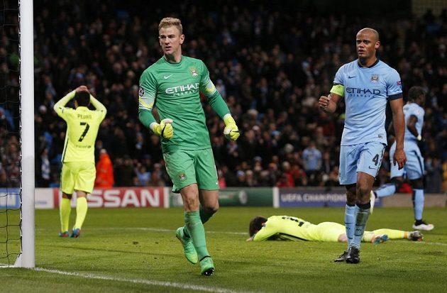 Brankář Joe Hart se raduje, vpravo obránce Manchesteru City Vincent Kompany. I on si oddechl, že barcelonský Lionel Messi (ležící) neproměnil v závěru penaltu ani dorážku.
