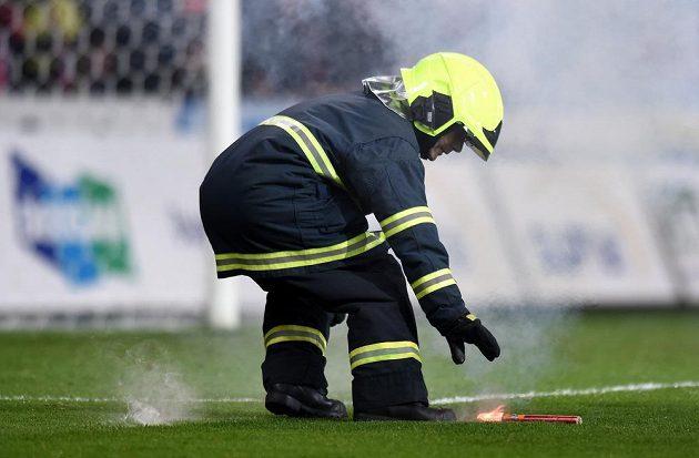 Hasič sbírá světlici na trávníku Doosan Areny během zápasu Plzně se Spartou.