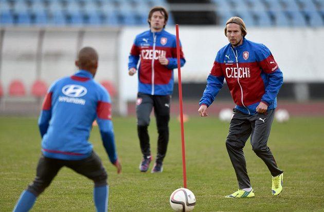 Jaroslav Plašil (vpravo) si na tréninku české fotbalové reprezentace přihrává míč s Theodorem Gebre Selassiem. Vzadu je Tomáš Rosický.