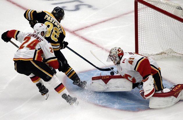 Český útočník Bostonu David Pastrňák zkouší překonat brankáře Calgary Mikea Smithe (41) v utkání NHL.