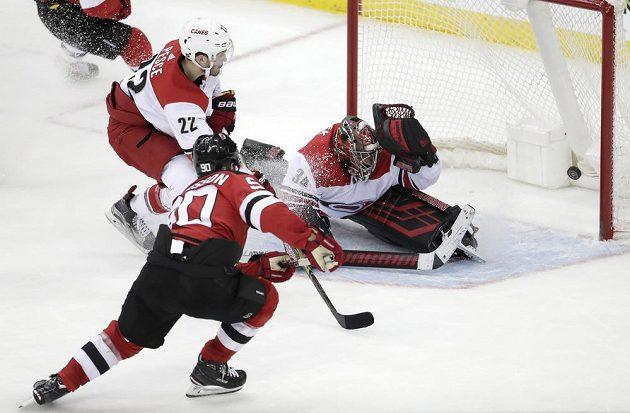 Útočník New Jersey Devils Marcus Johansson (90) překonává českého gólmana v brance Caroliny Petra Mrázka (34).