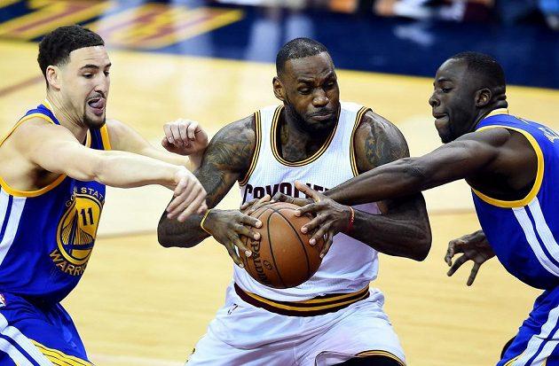 Hvězda Clevelandu LeBron James v sevření bránících hráčů Golden State Klaye Thompsona (vlevo) a Draymonda Greena.