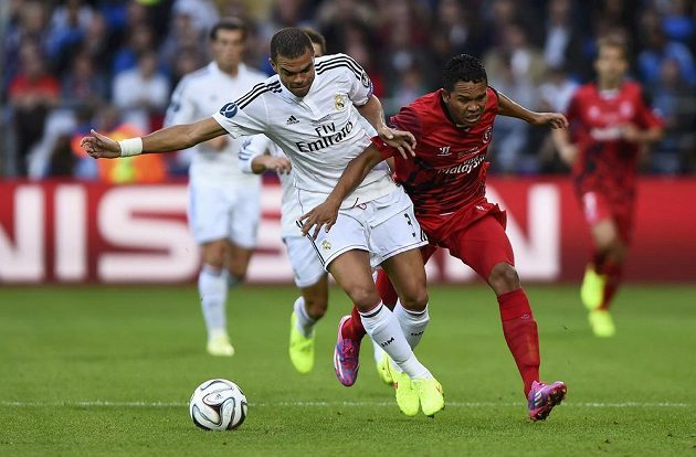 Obránce Realu Madrid Pepe (vlevo) zasahuje před Kolumbijcem Carlosem Baccou ze Sevilly.