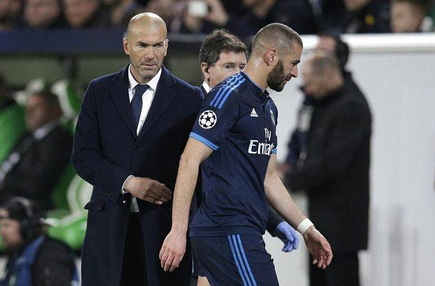Fotbalista Realu Madrid Karim Benzema vedle kouče Zinedina Zidana opouští hřiště na stadiónu Wolfsburgu po zranění.