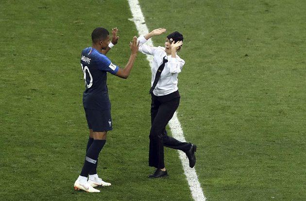 Francouz Kylian Mbappé si plácá s ženou, která během druhého poločasu finále vnikla na hrací plochu.