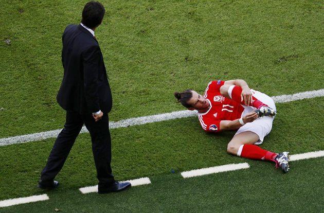 Velšský trenér Chris Coleman (vlevo) přichází ke své největší hvězdě Garethovi Balemu, který po jednom ze zákroků skončil na zemi.