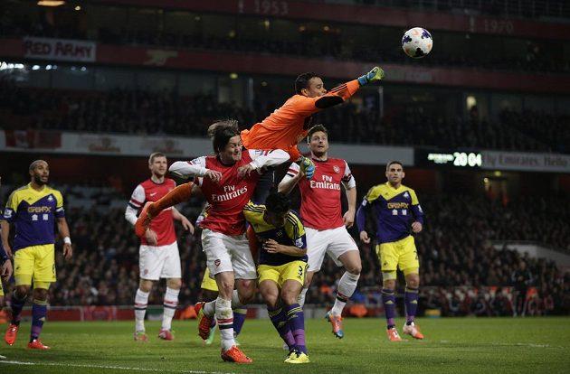 Brankář Swansea Michel Vorm vyráží míč nad Neilem Taylorem (č. 3) a Tomášem Rosickým z Arsenalu.