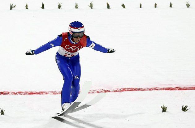 Český skokan na lyžích Roman Koudelka při doskoku během závodu na středním můstku.