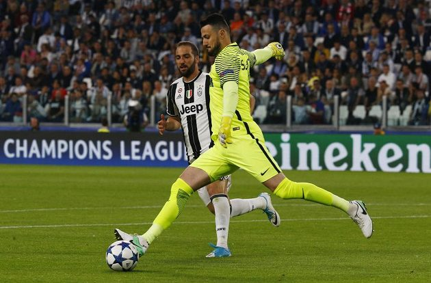 Brankář Monaka Daniel Subašic odkopává míč před Gonzalem Higuainem z Juventusu.