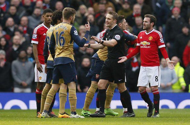Aaron Ramsey (16) z Arsenalu a Mata (8) z Manchester United při utkání anglické ligy, mezi nimi sudí Craig Pawson.