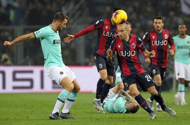 Fotbalista Boloně Rodrigo Palacio (vpravo) hlavičkuje míč před Stefanem De Vrijem z Interu Milán.