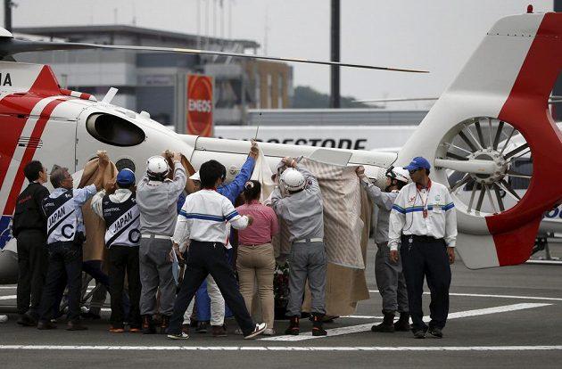 Pořadatelé nakládají vážně zraněného Alexa de Angelise do helikoptéry.
