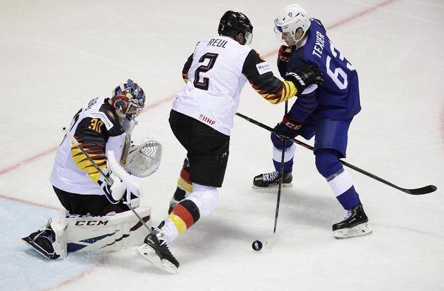 Brankář německé hokejové reprezentace Philipp Grubauer a německý bek Denis Reul se snaží zabránit tomu, aby se gólově prosadil Francouz Alexandre Texier.
