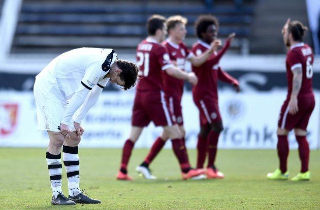 Zklamaný hradecký obránce Jakub Chleboun po inkasovaném gólu od Sparty, jejíž hráči oslavují.