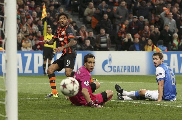 Luiz Adriano (vlevo) ze Šachtaru Doněck překonává brankáře Claudia Brava z Realu Sociedad, přihlíží Inigo Martinez.