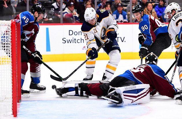 Kyle Okposo (21) z Buffala se pokouší dostat puk do sítě Colorada v utkání NHL. Na ledě je gólman Pavel Francouz.