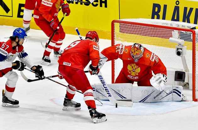Michael Frolík (vlevo) se snaží ohrozit ruského brankáře Andreje Vasilevského, uprostřed brání Dmitrij Orlov.