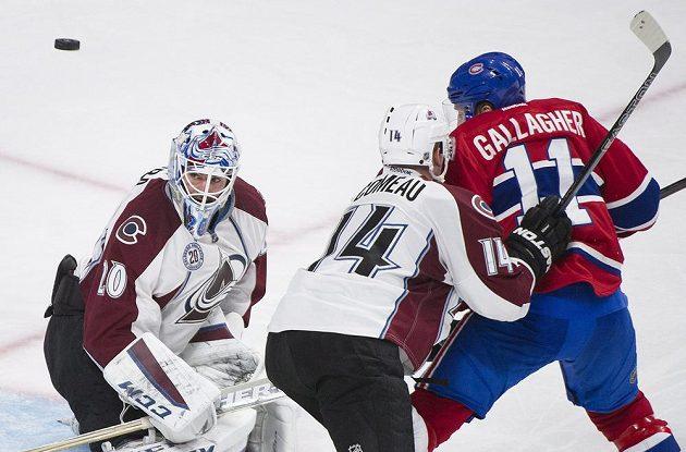 Kanadský útočník Montrealu Canadiens Brendan Gallagher (11) v souboji s Blakem Comeauem (14) z Colorada Avalanche. Brankář Colorada Reto Berra (20) sleduje letící puk.