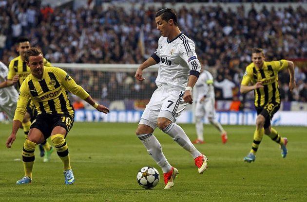 Cristiano Ronaldo, hvězda Realu Madrid, se proplétá mezi hráči Borussie Dortmund.