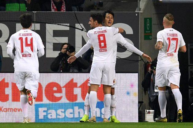 Fotbalista Augsburgu Ji Dong-won slaví se spoluhráči gól v síti slavného Bayernu Mnichov. Gratulovat spěchá i český fotbalista Jan Morávek.