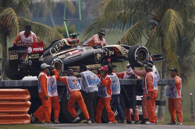 Obsluha na okruhu v Sepangu nakládá nepojízdný lotus Romaina Grosjeana.