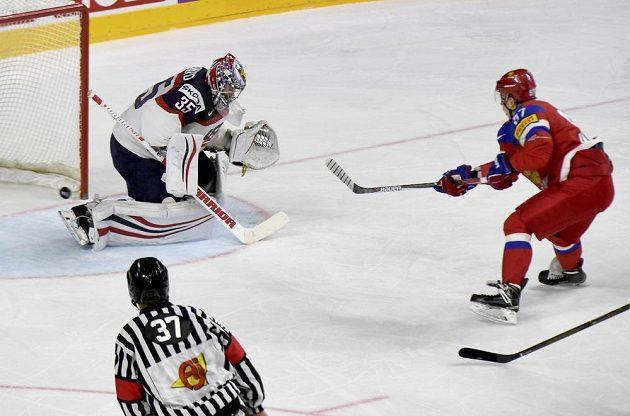 Ruský hokejista Nikita Gusev překonává amerického gólmana Jimmyho Howarda.