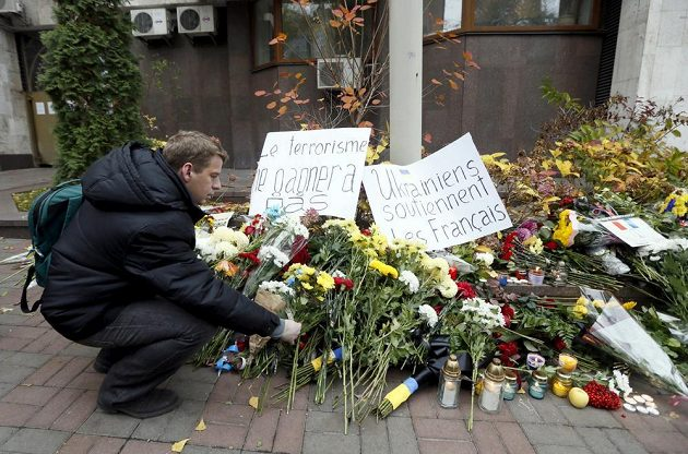 """Muž v ukrajinském Kyjevě pokládá blízko francouzského velvyslanectví květinu na pietní místo. Objevují se i vzkazy na podporu např. """"Ukrajinci podporují Francii""""."""