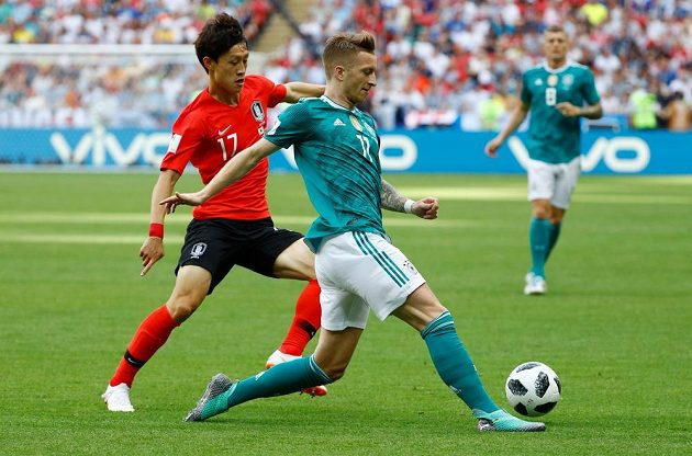 Německý reprezentant Marco Reus se snaží odehrát míč před dotírajícím Korejcem I Če-Songem v utkání mistrovství světa.
