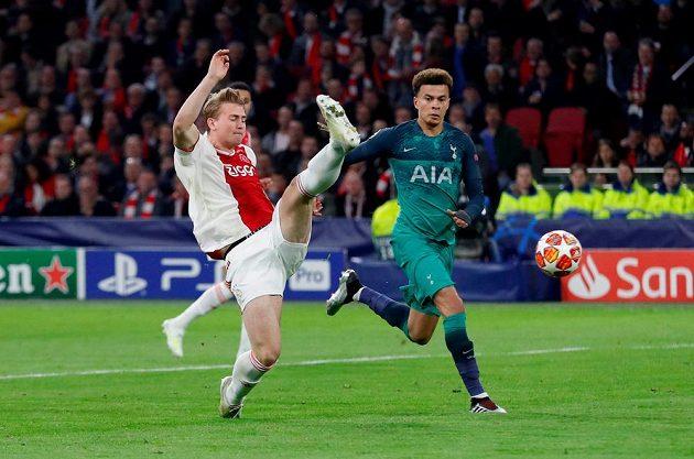 Matthijs de Ligt (vlevo) z Ajaxu ve snaze odkopnout míč, jeho počínání sleduje Dele Alli z Tottenhamu.