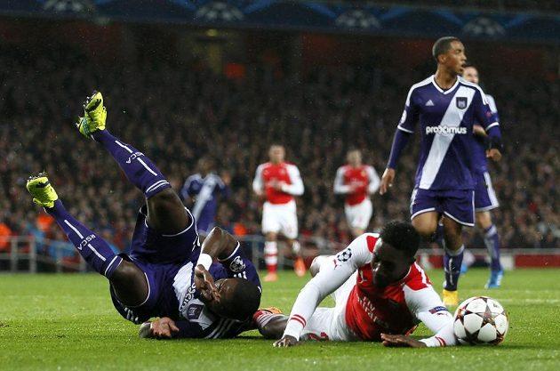 Fotbalista Arsenalu Danny Welbeck (vpravo) padá k zemi po faulu od Chancela Mbemby z Anderlechtu.