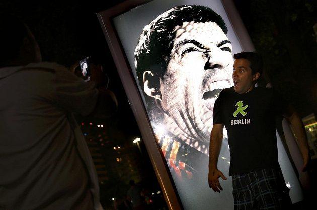 Fanoušek se fotí před reklamním billboardem, na kterém Luis Suárez cení zuby.