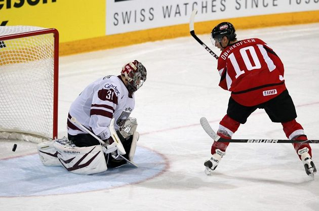 Rakouský hokejový útočník Daniel Oberkofler (vpravo) překonává lotyšského brankáře Edgarse Masalskise.