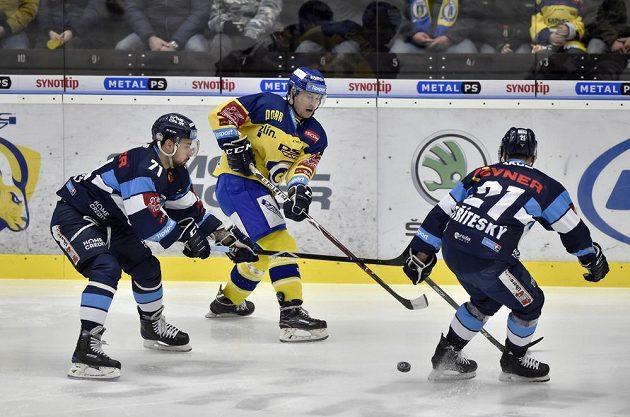 Zlínský hokejista Pavel Kubiš rozehrává puk přes bránící liberecké hráče Jakuba Valského a Matěje Stříteského v utkání extraligy.