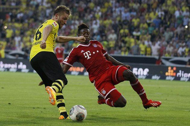David Alaba (vpravo) z Bayernu bojuje o míč s Jakubem Blaszczykowskim z Dortmundu.