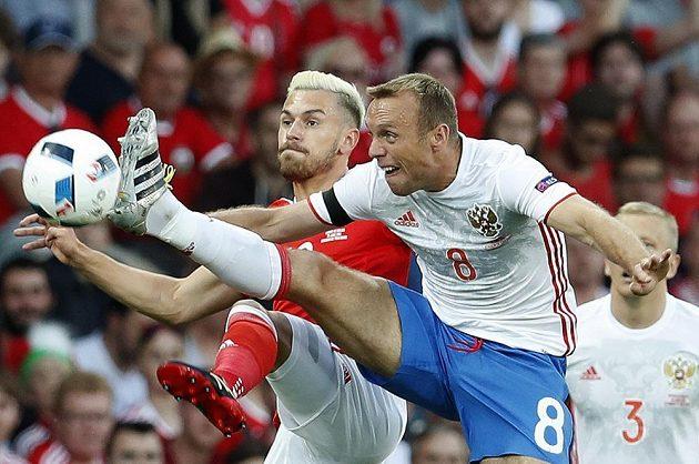 Rus Denis Glušakov (vpravo) v souboji o míč s Aaronem Ramseym z Walesu.