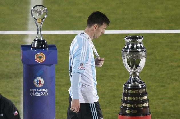 Argentinský kapitán Lionel Messi smutně prochází okolo trofeje pro vítěze Copy América (vpravo).