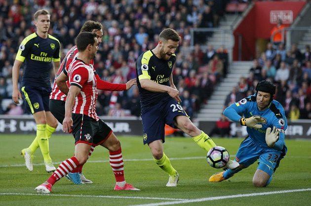Stoper Arsenalu Shkodran Mustafi odkopává míč před brankářem Petrem Čechem a dotírajícími hráči Southamptonu.