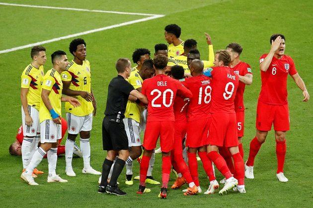 """Melu mezi fotbalisty Kolumbie a Anglie musel řešit hlavní rozhodčí Mark Geiger. Vlevo dole leží Jordan Henderson, kterému dal """"hlavičku"""" záložník Wilmar Barrios."""
