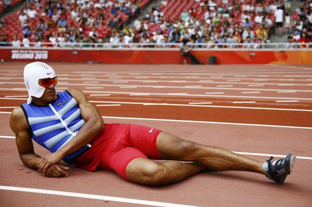 Americký desetibojař Ashton Eaton odpočívá během desetiboje na mistrovství světa v Pekingu i s chladící helmou na hlavě.