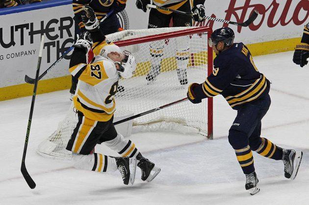 Kapitán Pittsburghu Sidney Crosby padá k ledu po zákroku Evandera Kanea z Buffala hokejkou do obličeje.